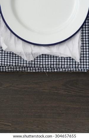 Vintage enamelware crockery on cloths on wooden background - stock photo