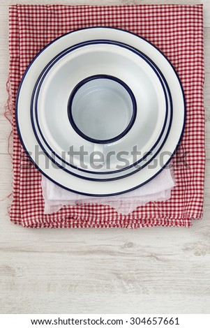 Vintage enamelware crockery on cloths on wooden background - stock photo