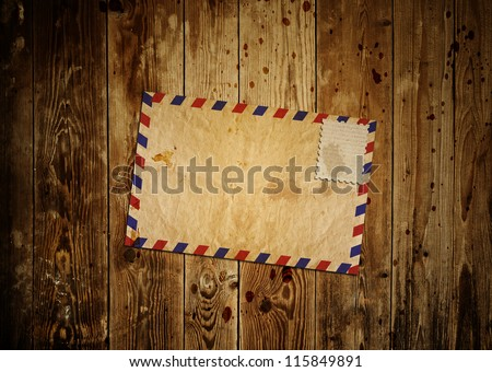 vintage envelop with blank stamp on wooden background - stock photo