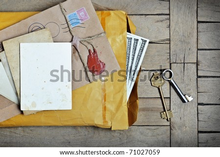 Vintage envelope with money empty photo paper and keys a on wooden surface - stock photo