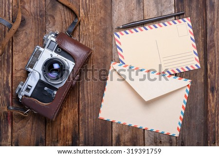 Vintage envelope with post card and retro camera on old wooden table - stock photo