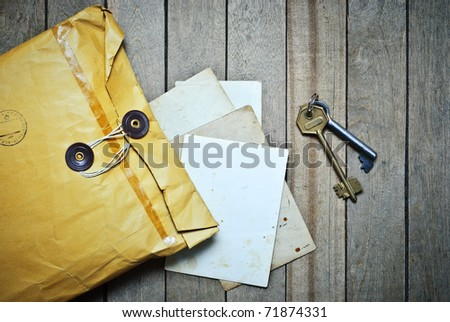 Vintage Envelopes with blanks photo paper and keys on a wooden table - stock photo