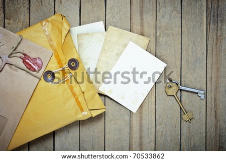 Vintage Envelopes with empty photos and keys on a wooden table - stock photo