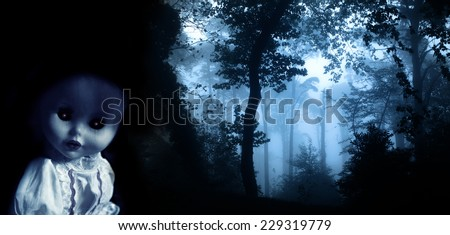 Vintage evil spooky doll and mysterious landscape of foggy forest  - stock photo