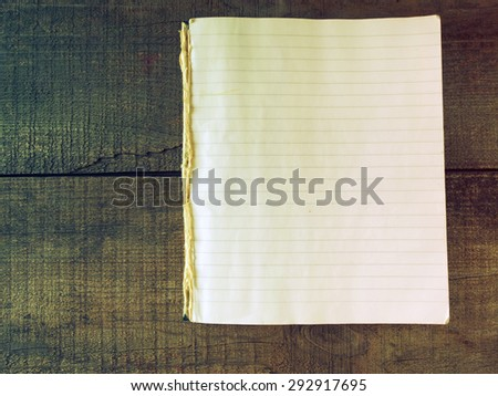 Vintage exercise book on wooden background - stock photo