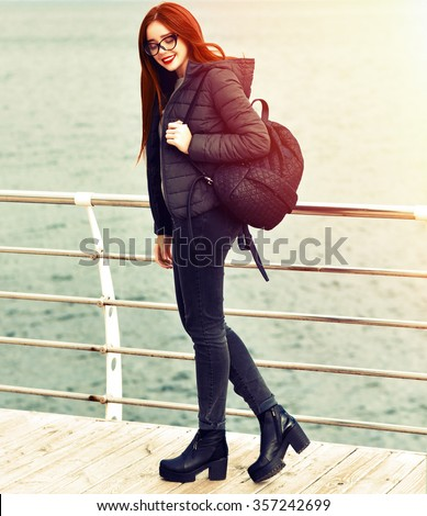 Vintage fashion lifestyle portrait of young cheerful smiling woman, spending amazing happy day near seaside, young traveler, hipster stile, hat sunglasses, cold weather, toned retro colors. - stock photo