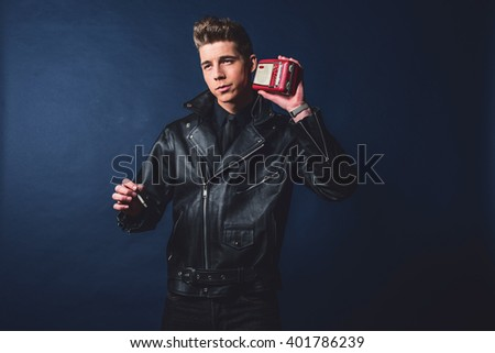 Vintage 1950 fashion man listening to portable radio. Wearing leather jacket and jeans. - stock photo