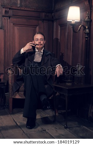 Vintage 1900 fashion man with beard and glasses. Sitting in old wooden reading room. Smoking pipe.