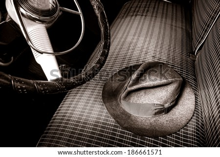 Vintage Fedora felt hat on an old fabric front car seat in an antique automobile in retro nostalgic sepia tone fashion  - stock photo