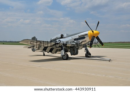 vintage fighter plane parked on the tarmac at a small airport - stock photo