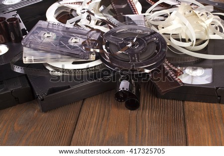 Vintage film camera rolls, old audio and video casettes with tape and foto strip on wooden table - stock photo