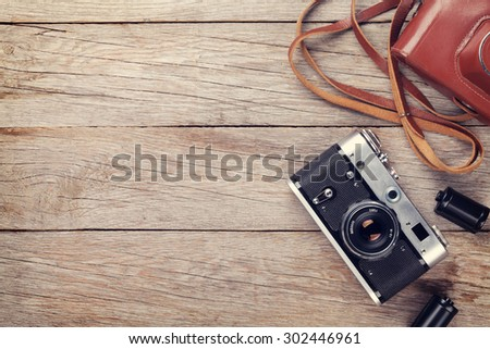 Vintage film camera with case on wooden table. Top view with copy space. Toned - stock photo