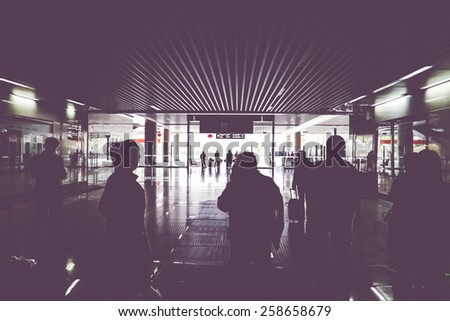Vintage filter : silhouette of passenger walking through train gate with light at the end of gate. - stock photo