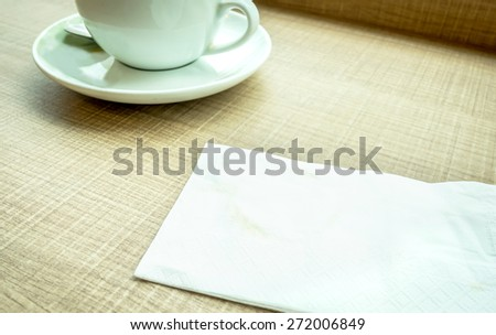Vintage filter : Tissue paper with coffee stain and coffee cup on wood table