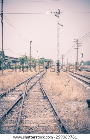 Vintage filter : Vacant Rail way switch track with yellow die grass. - stock photo