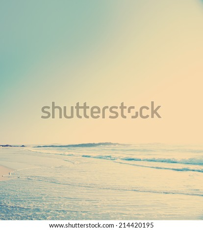 Vintage filtered beach photo of sand and waves with sky - stock photo