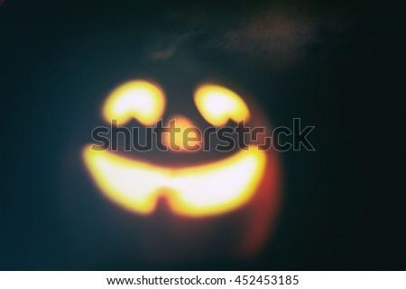 Vintage filtered defocused image of a smiling halloween jack o lantern pumpkin - stock photo