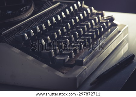 Vintage filtered Typewriter and pen on table.
