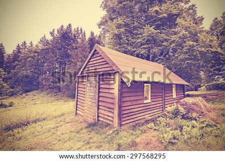 Vintage filtered wooden hut in forest, old film with vignette effect. - stock photo