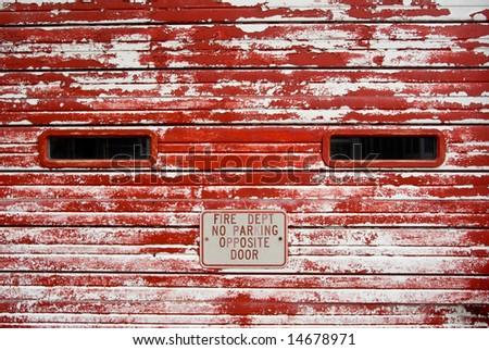 Vintage fire department wooden garage door with peeling, faded red paint - stock photo