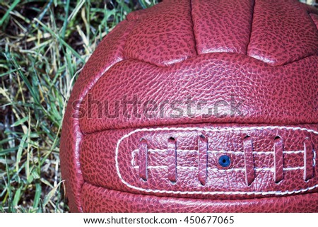 Vintage football over grass field, square image - stock photo