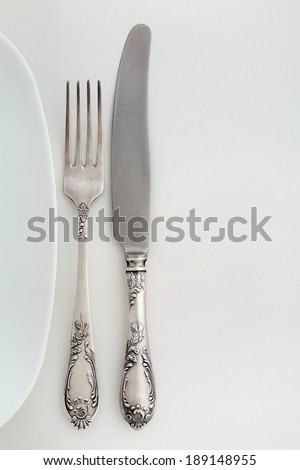 Vintage fork and knife near the plate. Overhead view. - stock photo