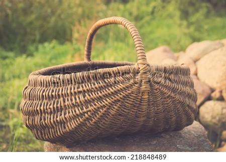 vintage foto of Empty basket / Braided basket basket on green lawn  - stock photo