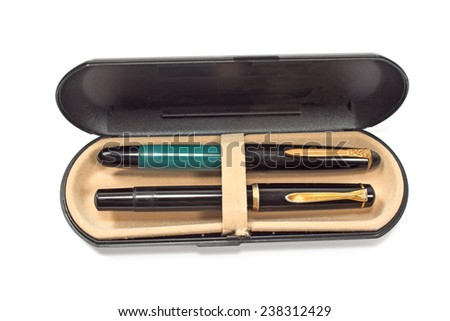 Vintage fountain pens in box isolated on white - stock photo