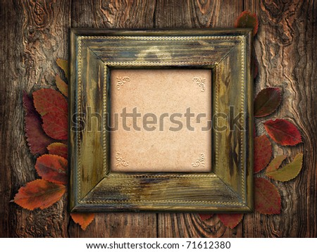 vintage frame with dry leaves on wooden background