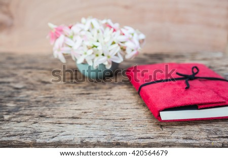 Vintage fresh flower in vase and red diary on wood table - stock photo