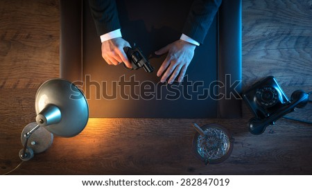 Vintage gangster holding a revolver and waiting while sitting at his desk at night, top view - stock photo