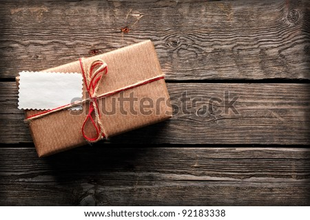 Vintage gift box (package) with address card on old wooden background. - stock photo