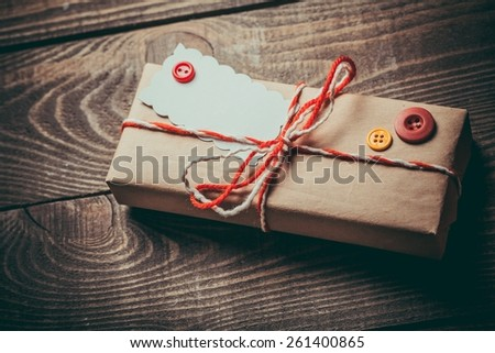 Vintage gift box (package) with blank gift tag on old wooden background. - stock photo