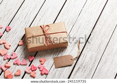 Vintage gift box with blank gift tag and heap of small hearts on white wooden background. - stock photo