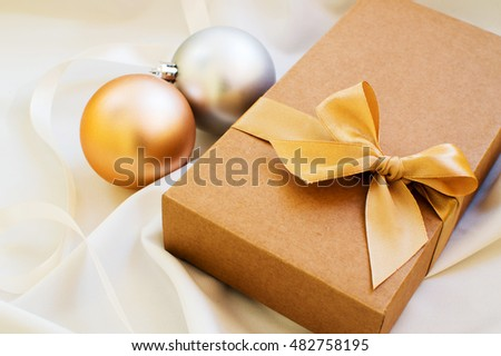 Vintage gift box with gold bow and with christmas balls on white fabric