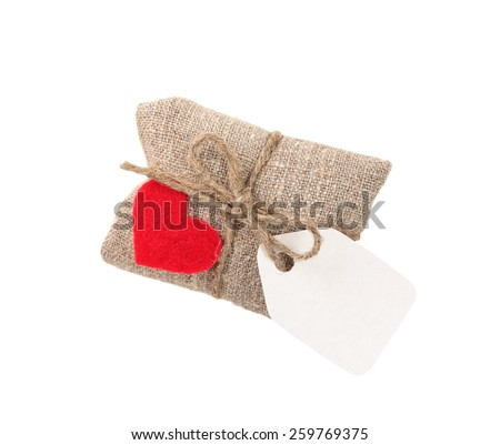 vintage gift in sacking with heart and tag, isolated on white - stock photo