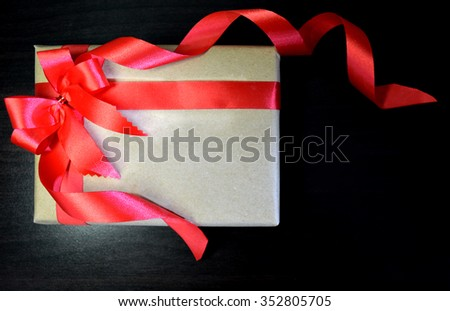 Vintage gift with red bow on black wooden background