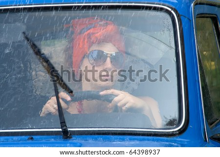 Vintage girl driving car under rain - stock photo