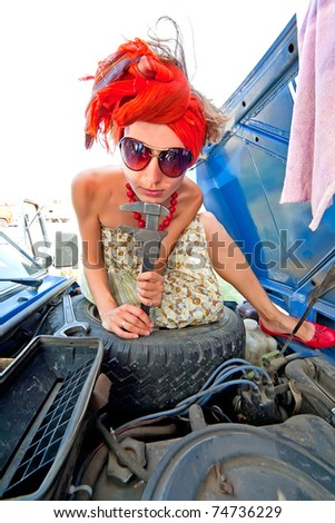 Vintage girl repairing car engine with wrench