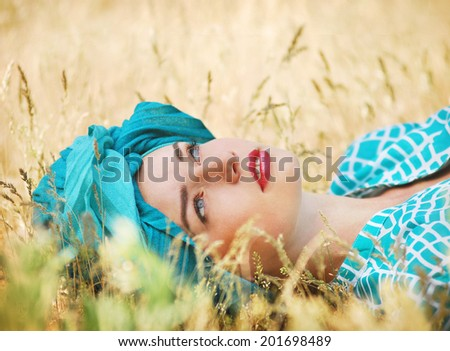 Vintage girl resting on a yellow field - stock photo