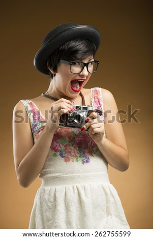 Vintage girl taking pictures using an old camera in a beige background  - stock photo