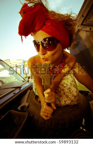 Vintage girl with tool repairing car - stock photo