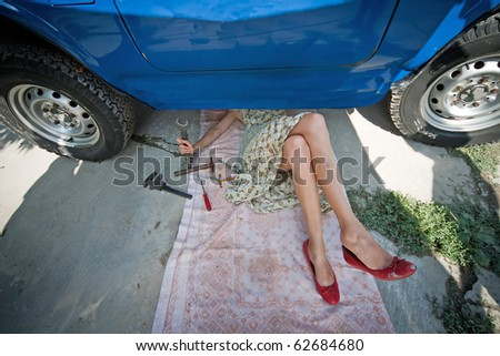 Vintage girl with tools repairing car - stock photo
