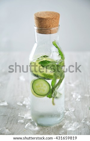 Vintage glass bottle filled with cold fresh cucumber mint lime lemonade like mojito witount alcohol, ideal drink for summer presented on table with melted ice - stock photo