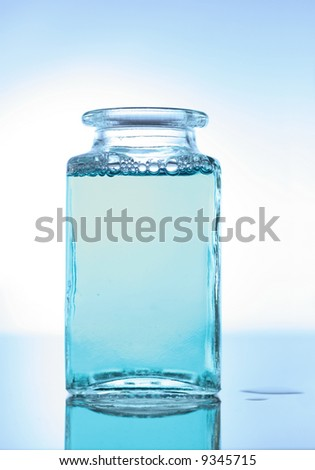 Vintage glass bottle with blue liquid, bubbles and reflection
