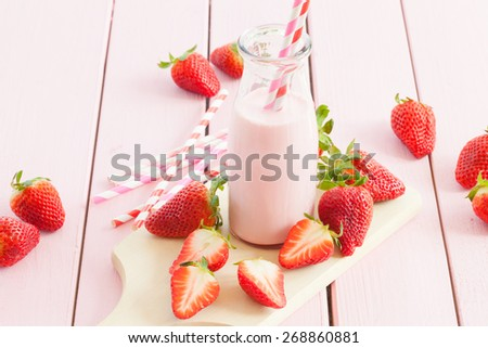 Vintage glass bottle with milk and fresh strawberries - stock photo