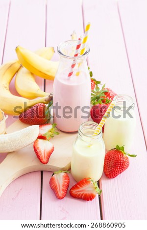 Vintage glass bottle with milk and fresh strawberries and bananas - stock photo