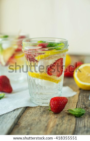 Vintage glass cups with homemade strawberry lemonade, served with fresh strawberries, mint and lime on the old  wooden table - stock photo