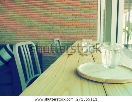 Vintage, glass of water on wood table bar background. - stock photo