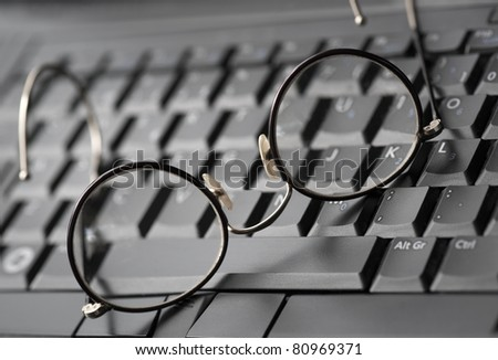 Vintage glasses on modern laptop keyboard